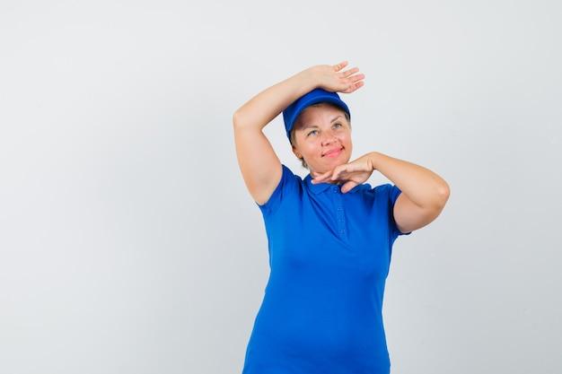 Femme mature montrant le geste de danse traditionnelle en t-shirt bleu et à mignon