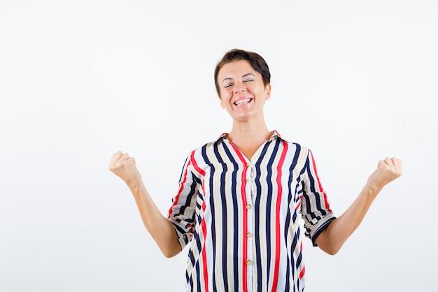 Femme mature montrant le geste du gagnant, les yeux fermés en chemise rayée et à la chance. vue de face.