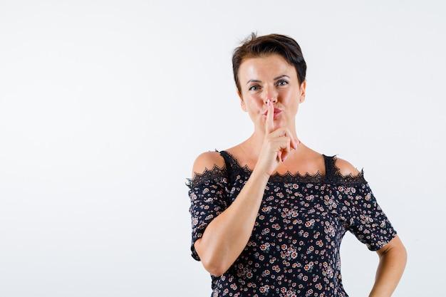 Femme mature montrant le geste de silence en chemisier floral, jupe noire et à la joyeuse, vue de face.