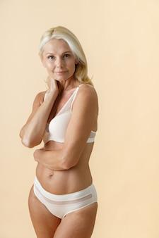 Femme mature naturelle aux cheveux blonds en sous-vêtements blancs regardant la caméra tout en posant isolé