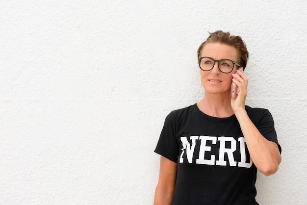 Femme mature nerd portant de grandes lunettes et debout isolé