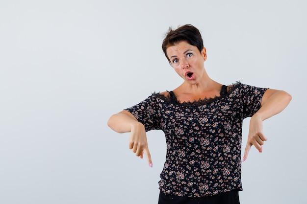 Femme mature pointant vers le bas en chemisier et à la perplexité. vue de face.