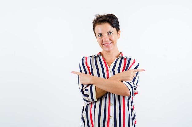 Femme mature pointant vers des directions opposées, souriant en chemisier rayé et à la vue de face, heureux.