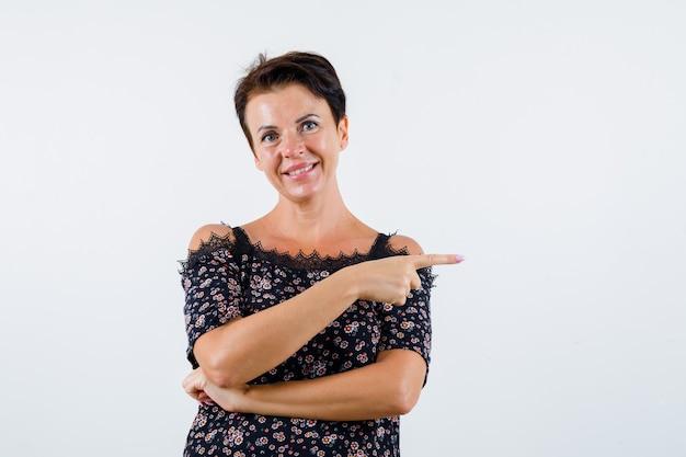 Femme mature pointant vers la droite avec l'index en chemisier floral, jupe noire et à la joyeuse vue de face