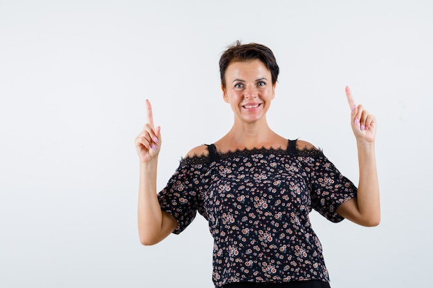 Femme mature pointant vers le haut avec l'index en chemisier floral, jupe noire et à la joyeuse. vue de face.
