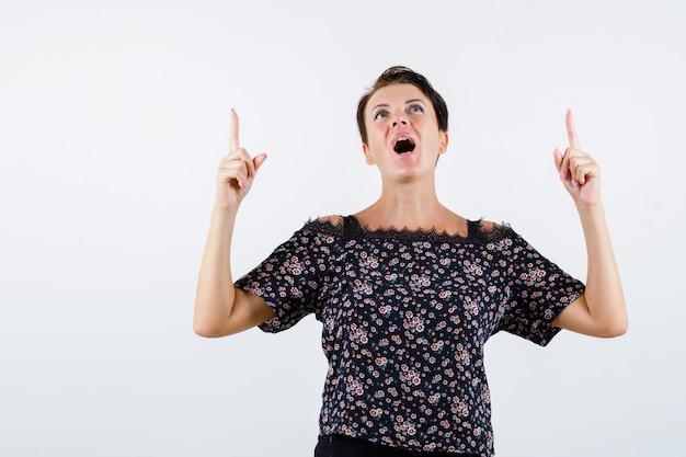 Femme mature pointant vers le haut avec l'index, gardant la bouche grande ouverte en chemisier floral, jupe noire et à la joyeuse. vue de face.