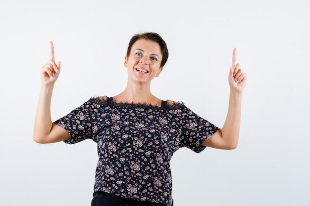 Femme mature pointant vers le haut tout en faisant la moue des lèvres en chemisier et à la joyeuse vue de face.