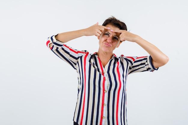 Femme mature popping un bouton en chemisier rayé et à la vue de face, focalisée.