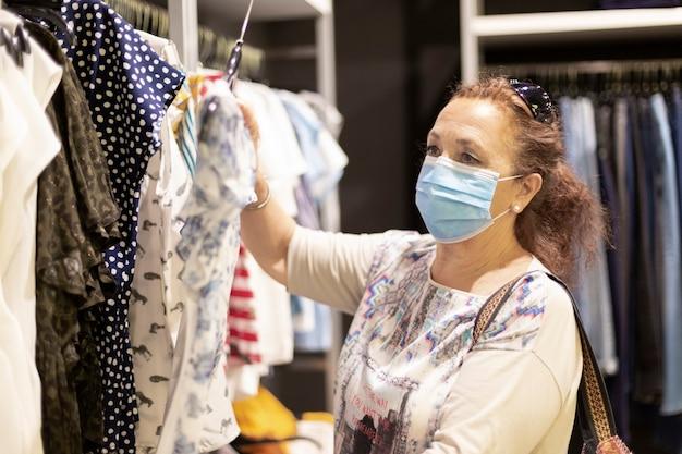 Femme mature portant un masque facial à la recherche de vêtements à l'intérieur d'un magasin.