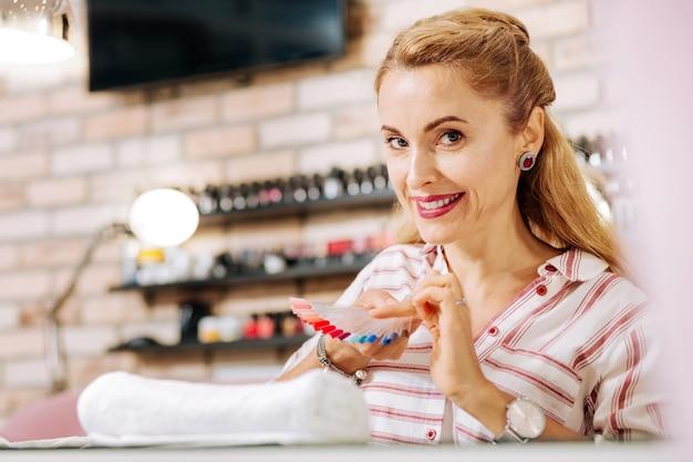 Femme mature positive regardant la caméra et optant la couleur du vernis à ongles