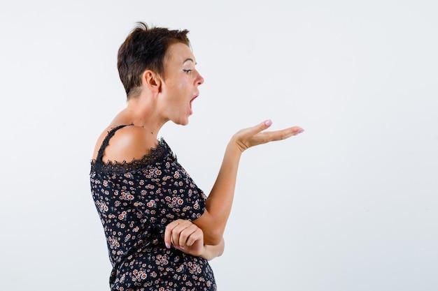 Femme mature qui tend la main comme tenant quelque chose, gardant la bouche grande ouverte en chemisier floral, jupe noire et à la surprise, vue de face.