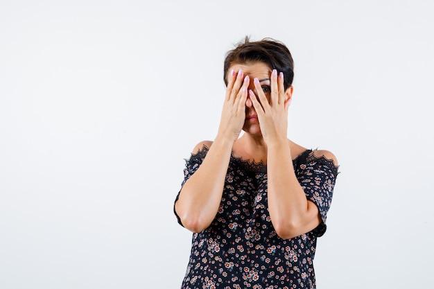 Femme mature regardant à travers les doigts en chemisier floral, jupe noire et à la vue de face, sérieuse