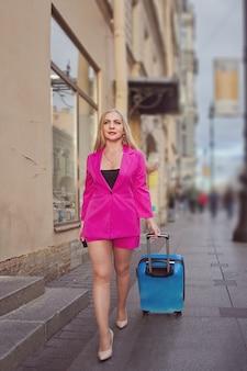 Femme mature en rose avec valise de voyage sur roues marche dans la rue.