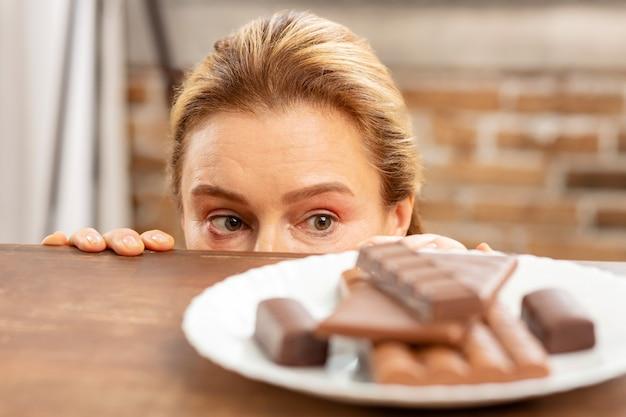 Femme mature se cachant et regardant le chocolat noir mais se sentant allergique