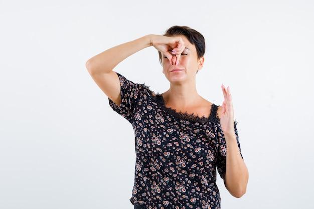 Femme mature se pincer le nez en raison d'une mauvaise odeur en chemisier floral, jupe noire et à l'irritation. vue de face.