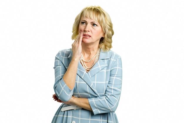 Femme mature se sentant mal aux dents. belle femme mature triste souffrant de fortes douleurs dentaires en se tenant debout sur blanc.