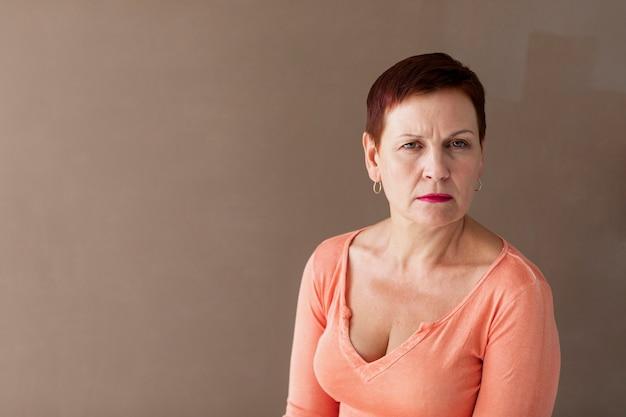 Femme mature sérieuse avec un fond uni