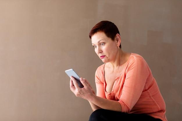 Femme mature avec un smartphone surpris
