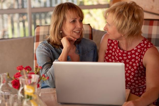 Femme mature avec son amie, son amie est assise devant un ordinateur portable et la regarde