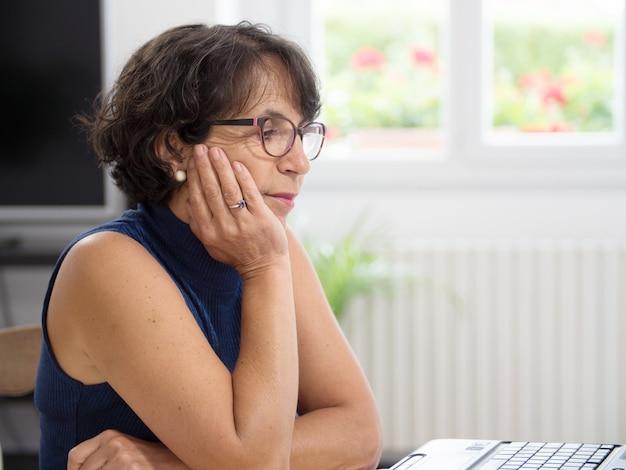 Femme mature avec son ordinateur portable dans la maison
