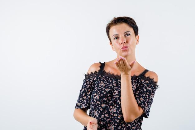 Femme mature soufflant baiser en chemisier floral, jupe noire et à la charmante. vue de face.