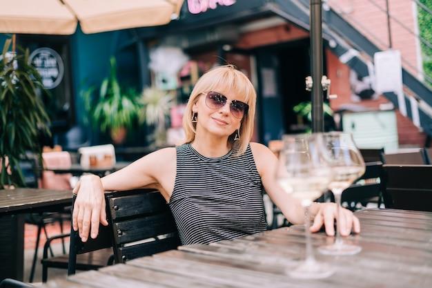 Femme mature souriante à lunettes assise sur un canapé dans un bar à l'extérieur avec des verres à vin et flou