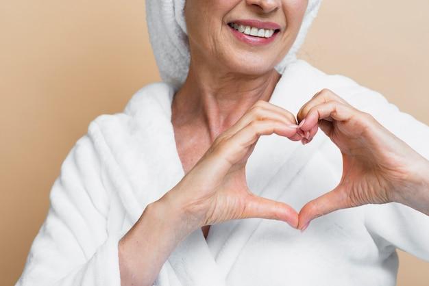 Femme mature souriante montrant l'amour