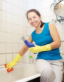 Femme mature souriante nettoie la baignoire