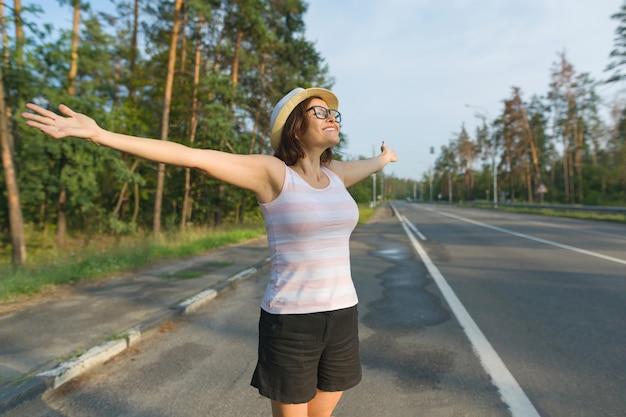 Femme mature souriante se tient sur la route, étend ses bras sur les côtés