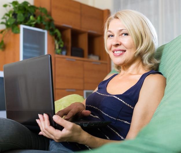 Femme mature souriante utilisant un ordinateur portable