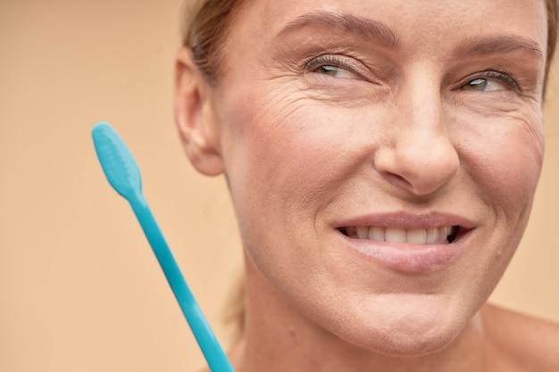 Femme mature souriante va se brosser les dents