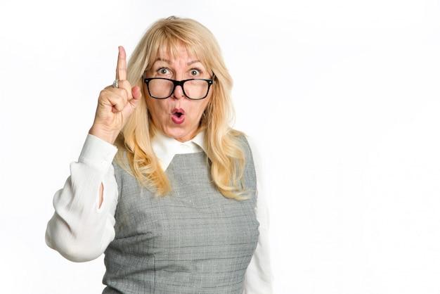 Une femme mature surprise avec des lunettes pointe le doigt vers le haut, isolé sur fond blanc.