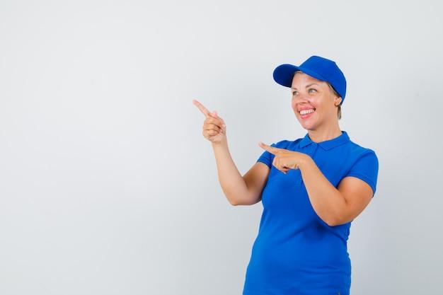 Femme mature en t-shirt bleu pointant vers le coin supérieur gauche et à la joyeuse.