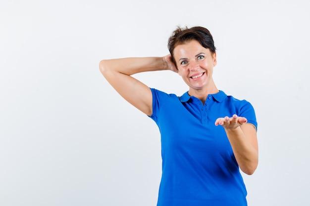 Femme mature en t-shirt bleu qui s'étend de la main, tenant l'autre main derrière la tête et à la vue de face, heureux.