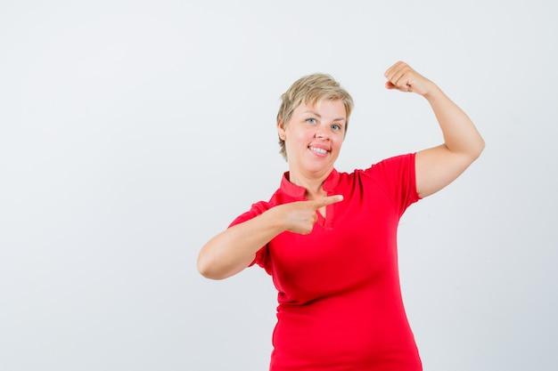 Femme mature en t-shirt rouge pointant sur les muscles du bras et à la confiance.