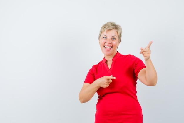 Femme mature en t-shirt rouge pointant vers le coin supérieur droit et à la bonne humeur.