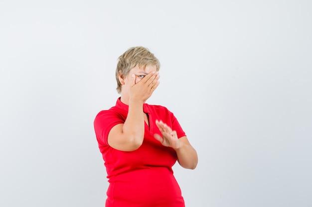 Femme mature en t-shirt rouge regardant à travers les doigts et à la gêne.