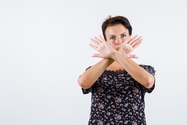 Femme mature tenant deux bras croisés, ne faisant aucun signe en chemisier floral, jupe noire et à la sérieuse. vue de face.