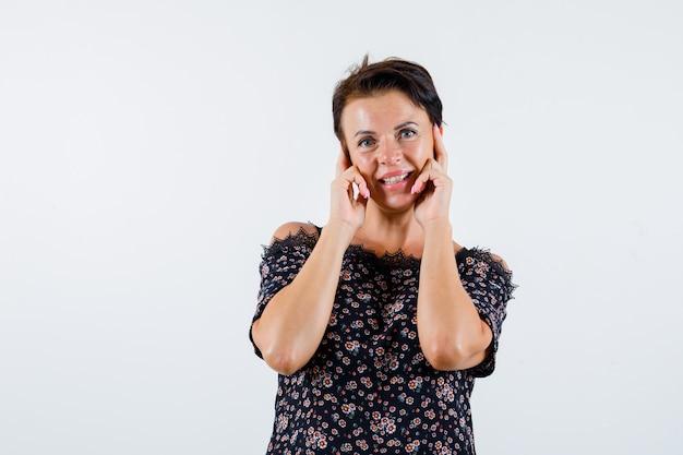 Femme mature tenant les index sur les joues en chemisier floral, jupe noire et à la joyeuse. vue de face.