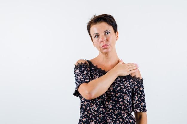 Femme mature tenant la main sur l'épaule en chemisier floral, jupe noire et à la recherche de sérieux. vue de face.