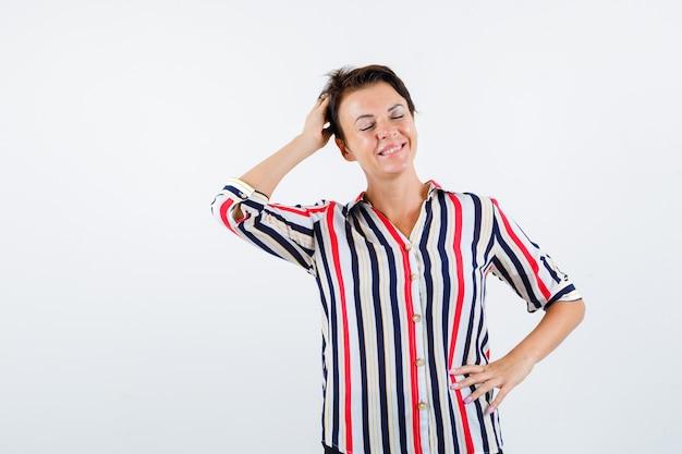 Femme mature tenant une main sur la taille, une autre main sur la tête, fermant les yeux en chemisier rayé et à la flottabilité. vue de face.