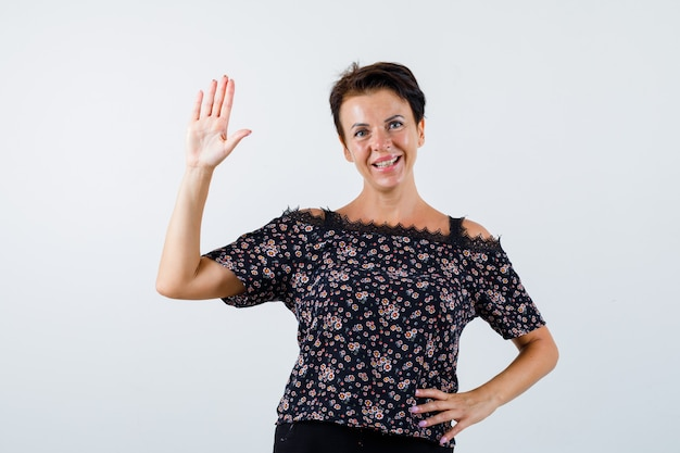 Femme mature tenant la main sur la taille, montrant le panneau d'arrêt en chemisier floral, jupe noire et à la joyeuse. vue de face.