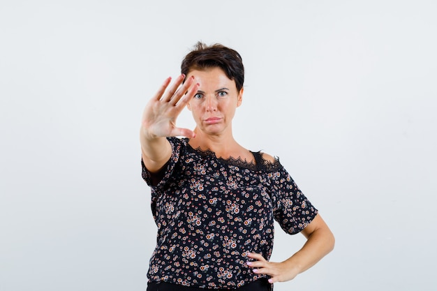 Femme mature tenant la main sur la taille, montrant le panneau d'arrêt en chemisier floral, jupe noire et à la vue de face, confiant.