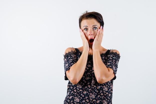Femme mature tenant les mains sur les joues, gardant la bouche ouverte en chemisier floral, jupe noire et à la surprise. vue de face.