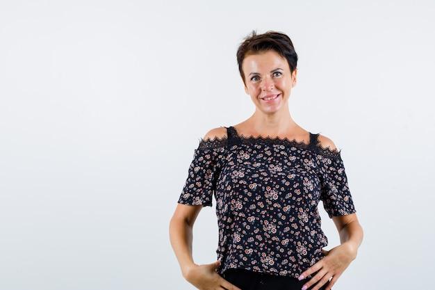 Femme mature tenant les mains sur la taille, souriant en chemisier floral, jupe noire et à la joyeuse. vue de face.