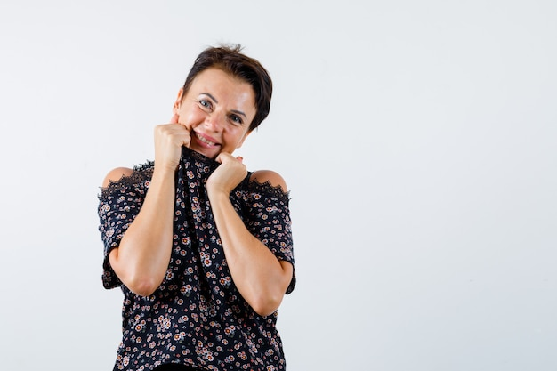 Femme mature tirant le col sur le menton en chemisier à fleurs, jupe noire et à la joyeuse, vue de face.