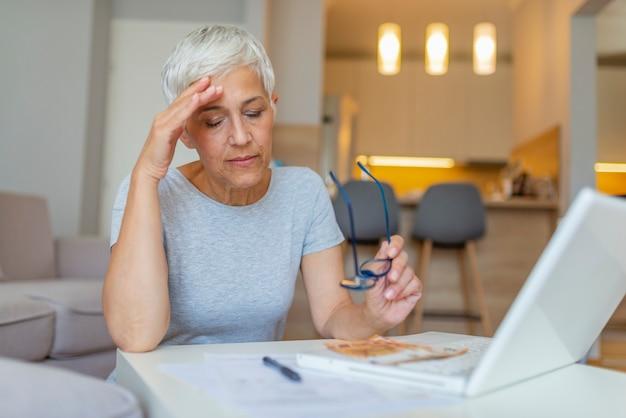 Femme mature travaillant avec des documents à table à la maison.