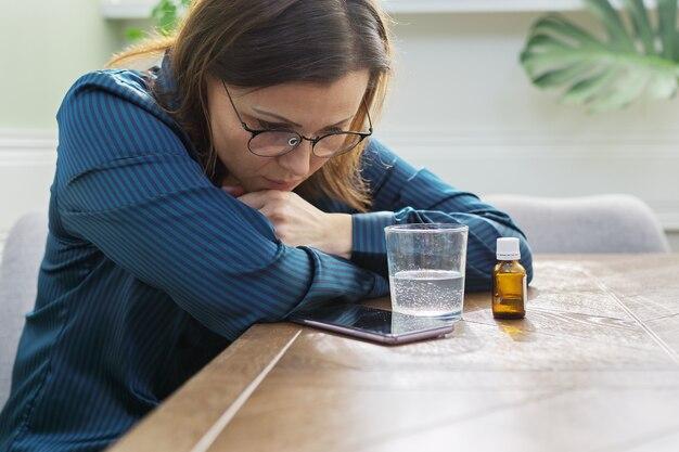 Femme mature triste grave avec des médicaments, un verre d'eau et un téléphone