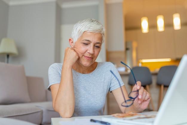 Femme mature vérifiant les factures à la maison.