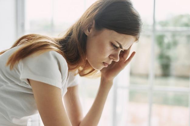 Femme de maux de tête à la maison problèmes intérieurs trouble de la solitude migraine